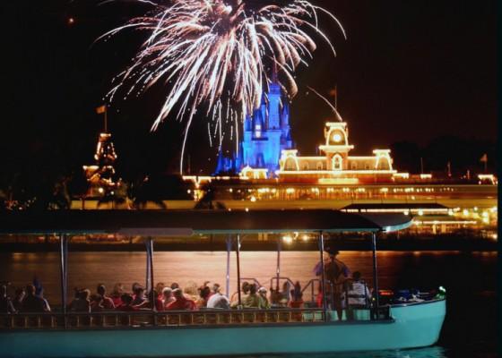 Foto dos fogos e do Magic Kingdom iluminado, além do barco, durante o Pirates & Pals Firework Voyage