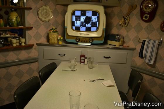 Foto da mesa o 50s Prime Time Café, com a TV antiga ao lado e os arredores imitando uma cozinha dos anos 50