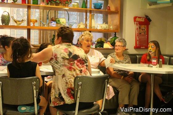 A Sue, a garçonete, conversando com duas famílias em outras mesas