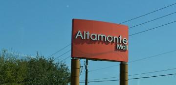 Foto da placa do Altamonte Mall, em Altamonte Springs. Ela é vermelha com letras cinza e o céu está azul ao fundo
