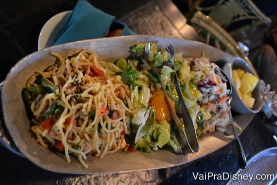 A salada que vem divida em 3 partes: mix de folhas com alguns gomos de tangerinas em conserva, uma salada de macarrão e uma salada de repolho.