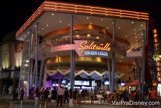Foto do exterior do Splitsville mostrando as mesas e o letreiro iluminado do restaurante e pista de boliche através das paredes de vidro.