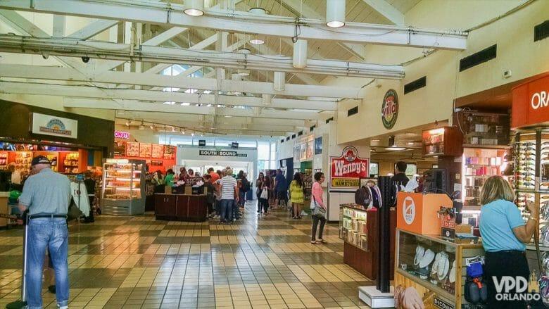 Foto da praça de alimentação entre Orlando e Miami, com diversos restaurantes e pessoas transitando