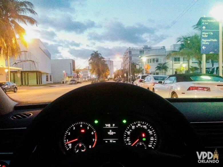 Dá pra ir de Miami para Orlando sem pagar pedágio. Foto tirada de trás do volante do carro, mostrando uma cidade ao entardecer, com algumas luzes já acesas