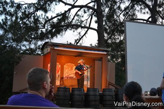 Foto do cantor no palco com o violão durante a parte das cantigas do Campfire