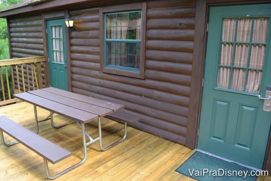 Foto da varanda da cabine no Fort Wilderness, toda de madeira e com as portas pintadas de verde-escuro. Há uma mesa de madeira com banco para os visitantes se sentarem