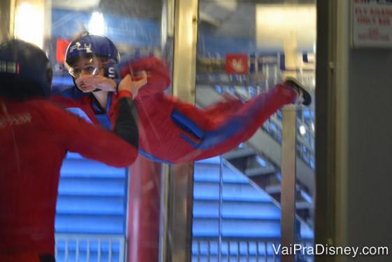 Foto da Renata no simulador de voo de para-quedas iFly em Orlando, flutuando com uma instrutora por perto