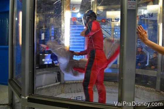 Foto de um visitante no simulador de voo com uma instrutora por perto, durante o treinamento