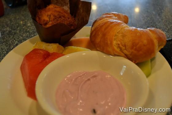 Foto de um prato com um croissant, iogurte de morango e um muffin