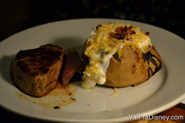 Foto do prato com uma carne e uma batata recheada transbordando catupiry.