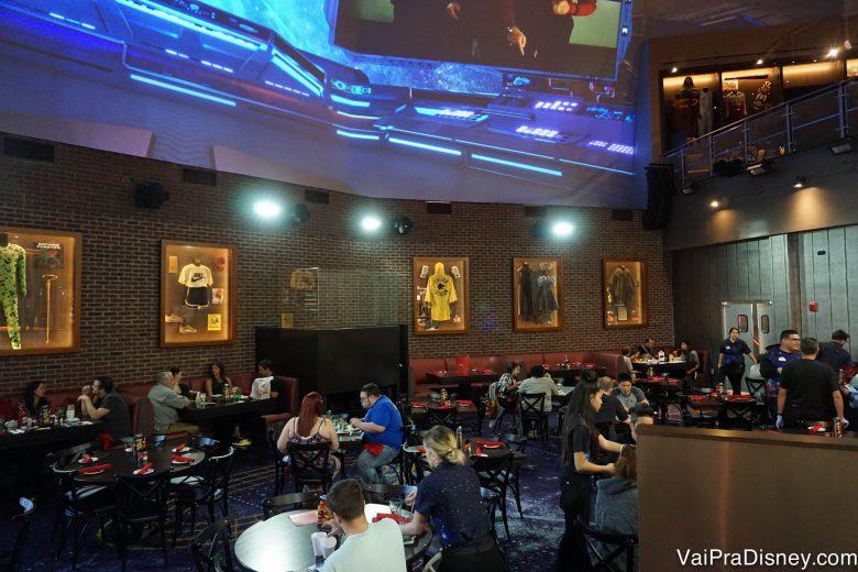 Outra parte da área interna do Planet Hollywood, com mesas e um telão acima passando clipes