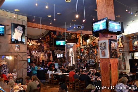 O interior cheio e bagunçado do restaurante, com várias mesas e muita decoração nas paredes