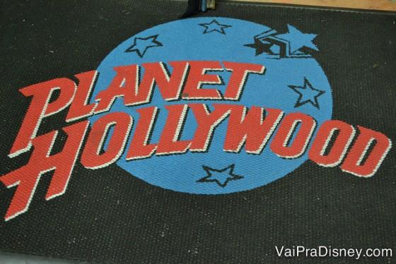 O símbolo do Planet Hollywood, azul e vermelho, no cardápio de fundo preto