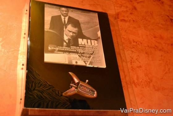 """Cartaz de MIB com o """"apagador de memória"""" exposto embaixo, na parede"""
