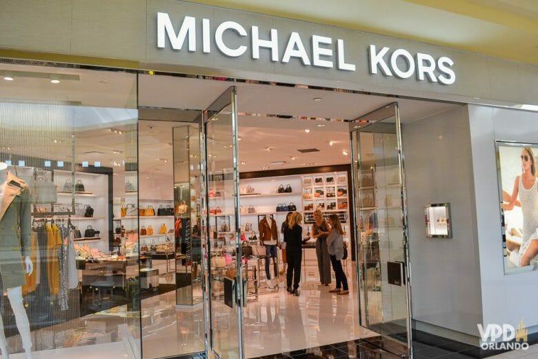Vitrine de bolsas na Michael Kors. As mulheres piram e gostam muito de gastar nessa loja! Foto da vitrine da loja Michael Kors, com algumas roupas à vista.