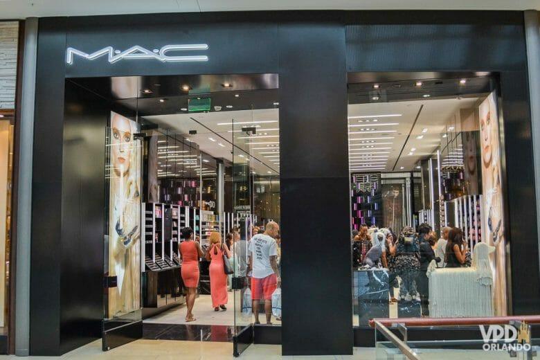Vale checar os valores da MAC aqui no Brasil e ver se compensa comprar em Orlando! Foto da vitrine da loja da MAC em Orlando, com alguns visitantes dentro.