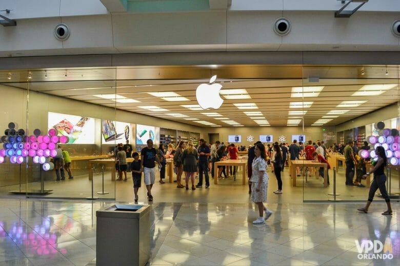 Apple, uma das principais lojas para gastar os seus dólares! Foto da loja da Apple em Orlando, cheia de visitantes entrando, saindo e dentro.