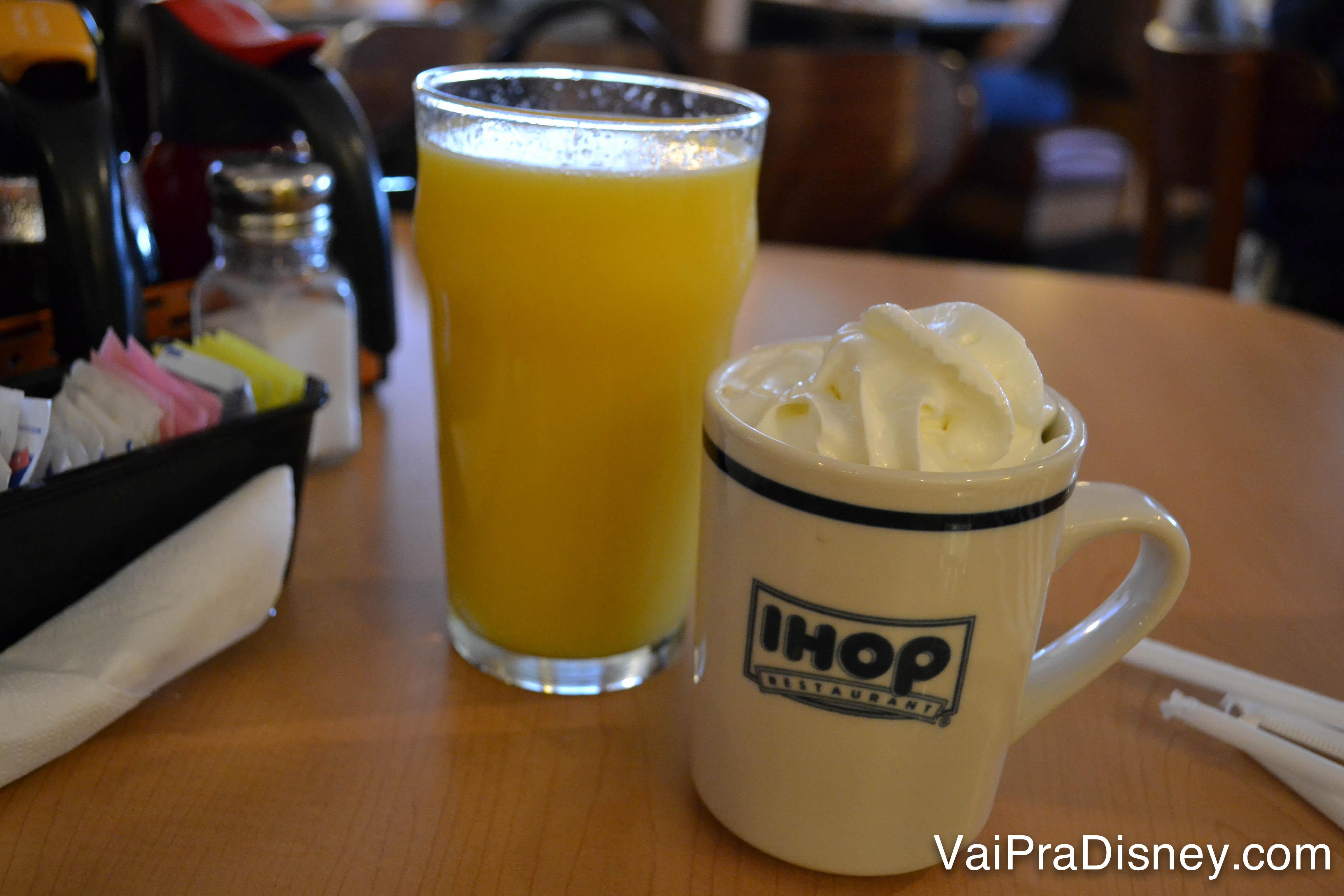 Foto de um suco de laranja no copo, ao lado de uma xícara de chocolate quente com chantilly em cima