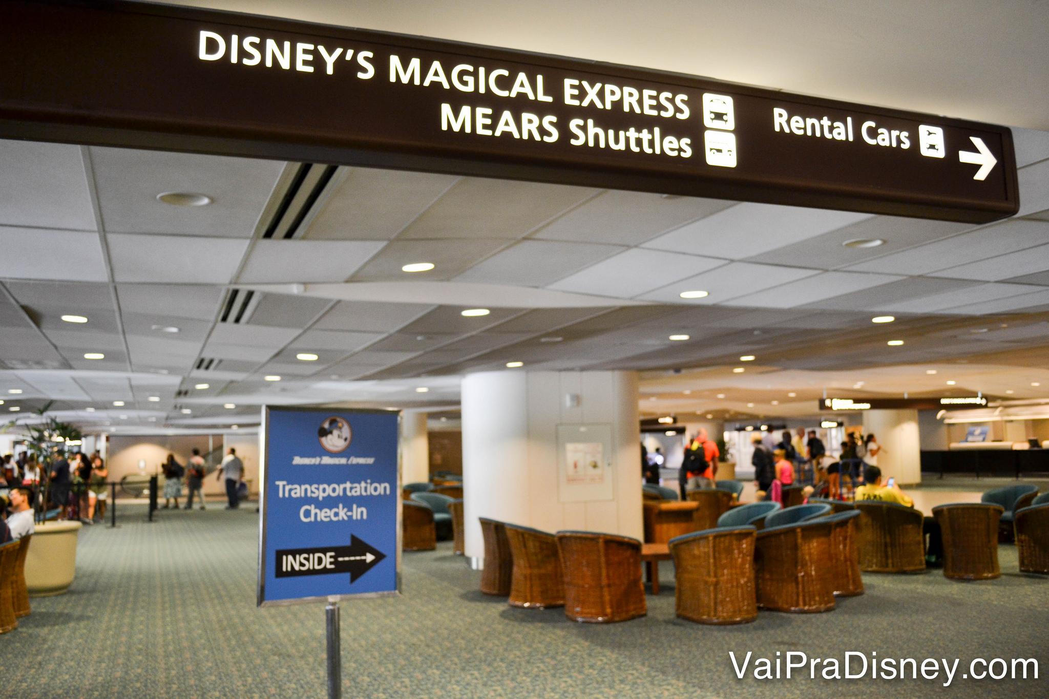 Placas no primeiro andar do aeroporto que indicam onde pegar o transporte da Disney e aonde ir para as locadoras de carro.