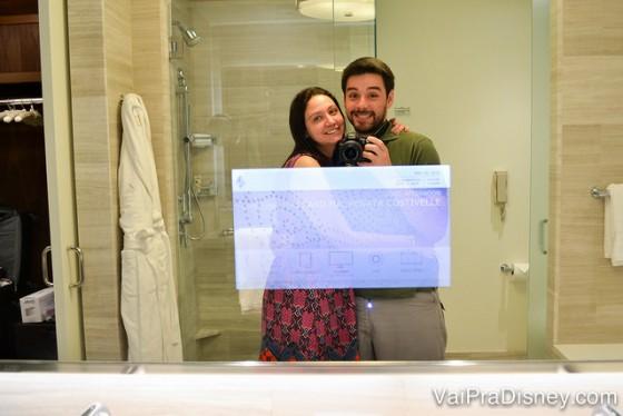 Foto da Renata e do Felipe no espelho do banheiro, mostrando que ele tem uma TV no meio