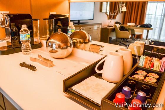 Foto da mesa no quarto com a cafeteira Nespresso e cápsulas