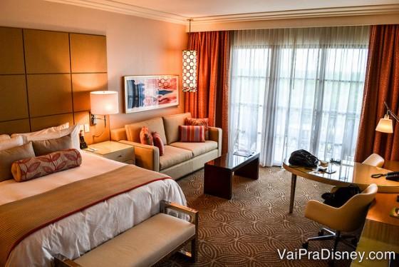 Foto do quarto do Four Seasons, com uma cama king, sofá, escrivaninha e decorado em tons quentes