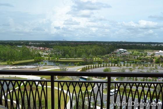 Foto do hotel visto da varanda do quarto - o estacionamento, parte do lago e as árvores