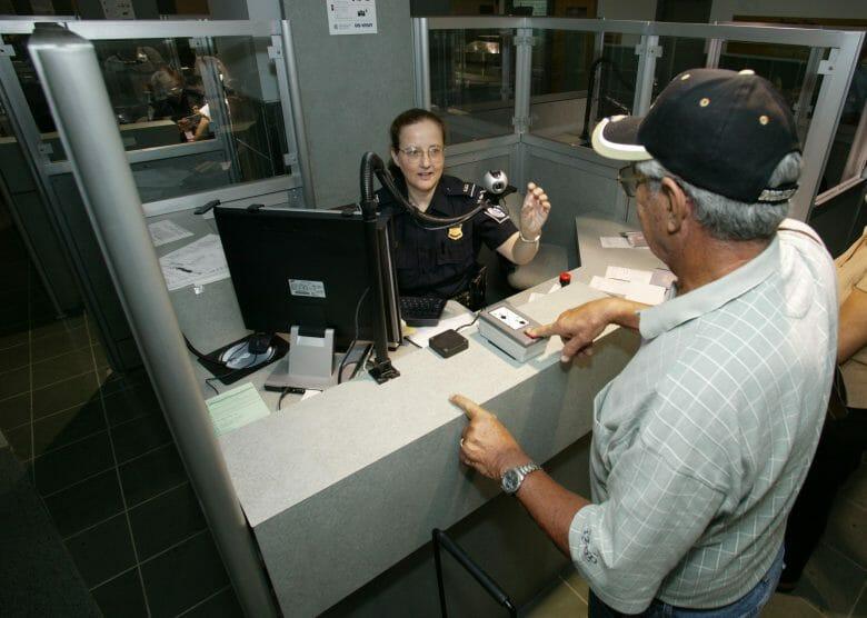 Imagem de uma oficial da imigração dos EUA no ponto de controle de passaporte, atendendo um passageiro.