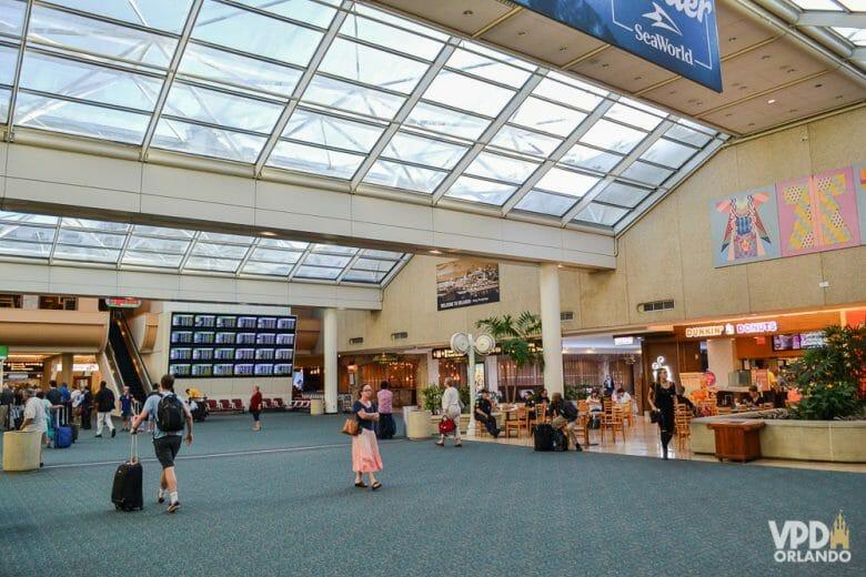 Foto do saguão do aeroporto de Orlando. É possível ver algumas lojas, passageiros e uma escada rolante.