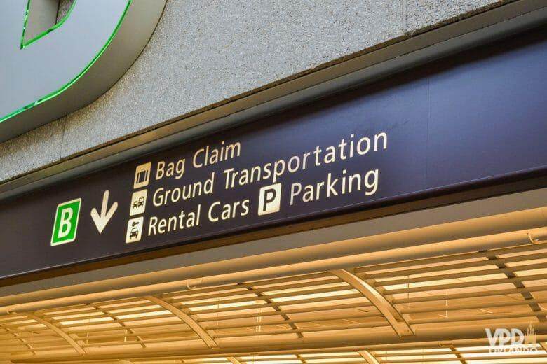 Chegando no terminal, você pode pegar as suas bagagens, retirar o carro alugado ou pegar o transporte da Disney! Foto da placa do terminal B no aeroporto de Orlando.