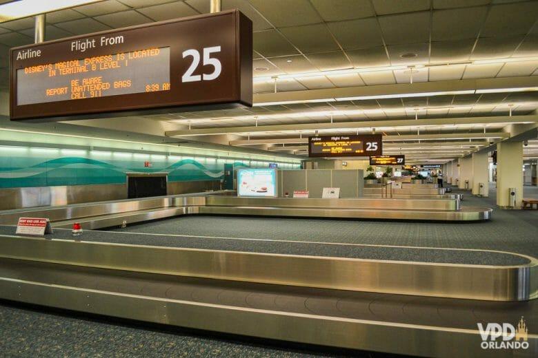 Foto da esteira de bagagem no aeroporto de Orlando, com a placa indicando as informações dos voos acima.