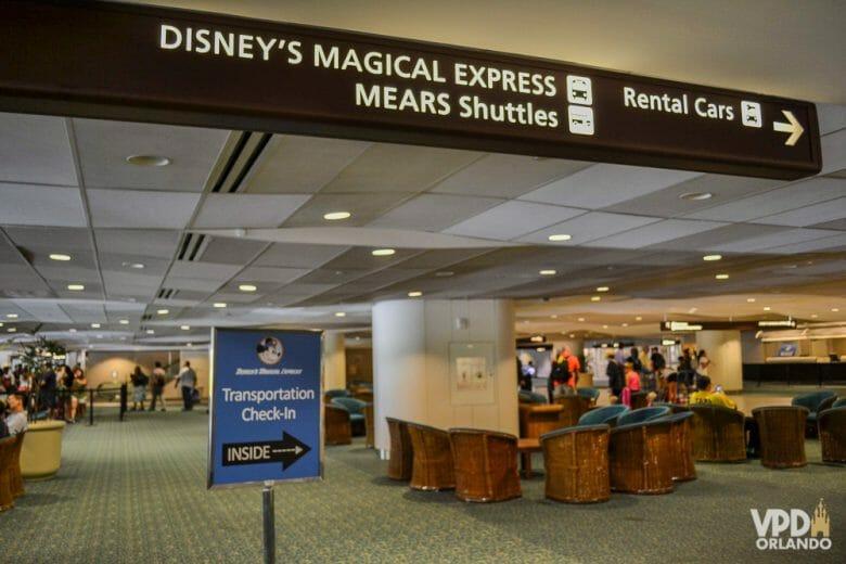 """Foto das placas no primeiro andar que indicam onde pegar o transporte da Disney (uma placa com o Mickey) e aonde ir para as locadoras de carro (a placa diz """"Rental Cars"""")"""