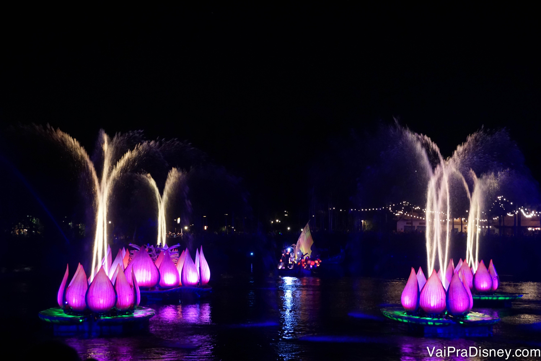 Foto do show noturno do Animal Kingdom, o Rivers of Light. Há vitórias-régia gigantes e cor-de-rosa no lago, com fogos saindo de dentro delas.