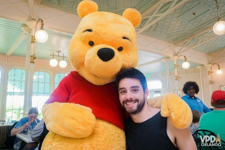 O Crystal Palace no Magic Kingdom tem café, almoço e jantar com personagens da turma do Pooh. Foto do Felipe abraçado ao Pooh na mesa do Crystal Palace.