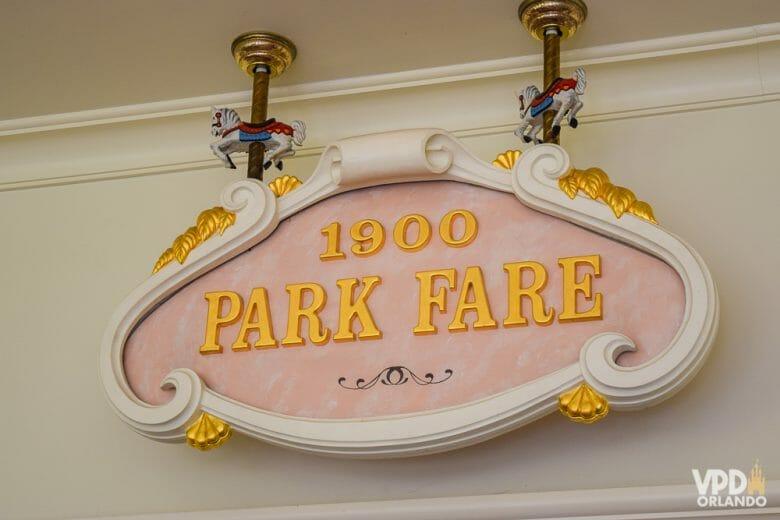 O café da manhã do 1900 Park Fare é um dos nossos preferidos da Disney! Foto da placa na entrada do restaurante 1900 Park Fare, com o fundo rosa claro e as letras em dourado