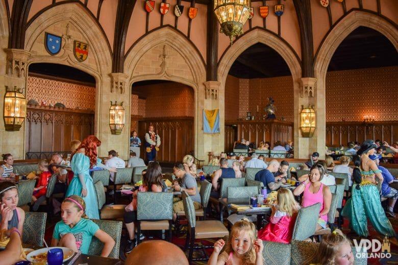 Como reservar restaurante na Disney - As refeições com princesas no Cinderella's Royal Table são pagas no momento da reserva. Foto das mesas com vários visitantes no Cinderella's Royal Table, e as princesas passando entre elas para tirar fotos