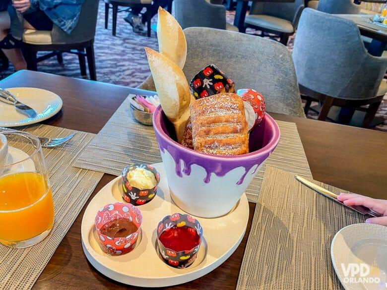 Café da manhã do Topolino's Terrace. Foto do prato no café da manhã no Topolino's Terrace, com uma cesta de pães e potinhos de geleias