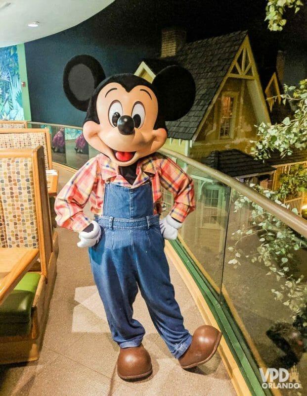 O Garden Grill no Epcot tem um almoço bem gostoso com o Mickey na versão fazendeiro! Fofo, né? Foto do Mickey no Garden Grill, no Epcot, com uma jardineira jeans, camisa xadrez e botas.