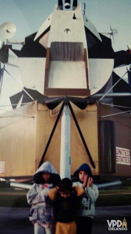 Eu com 7 anos visitando o KSC pela primeira vez, junto com meu irmão e com a minha prima. Eu sou o único destemido mostrando o rosto. Foto do Felipe  pequeno com mais duas crianças em frente a um foguete no Kennedy Space Center
