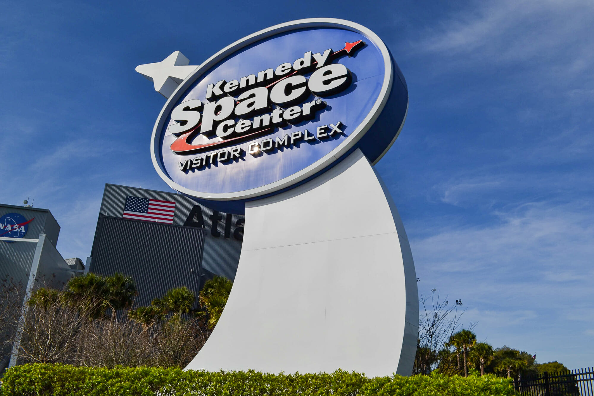 Foto da placa na entrada do Kennedy Space Center, que tem o logo do local e um foguete branco ao lado.