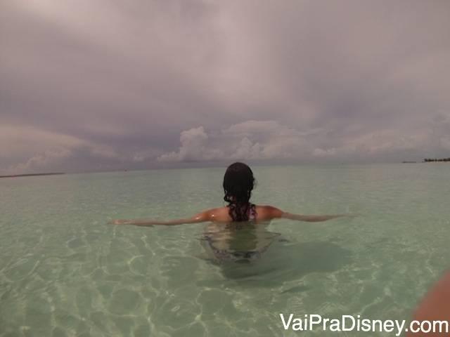 Foto da Renata de costas no mar transparente em Serenity Bay, a praia só para adultos nas Bahamas
