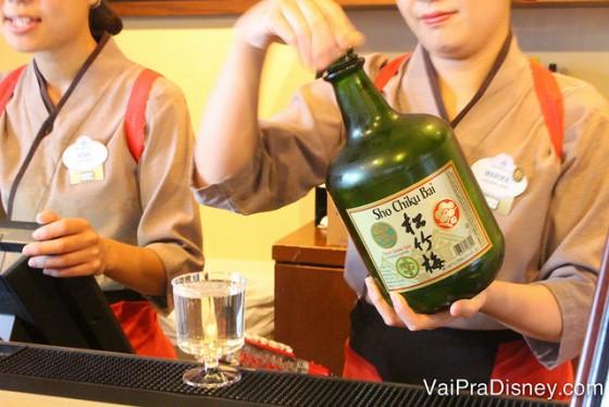 Foto de uma atendente servindo saquê no pavilhão do Japão durante o Drinking Around the World