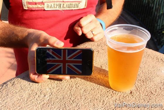 Foto do drinque ao lado da bandeira do país no celular, que o amigo da Rê tirou para manter organizado. No caso, uma bandeira do Reino Unido ao lado de um copo de cerveja