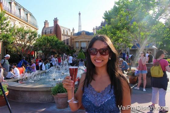 Foto da amiga da Renata, a Cati, com uma taça de champagne e o pavilhão da França ao fundo no Drinking Around the World