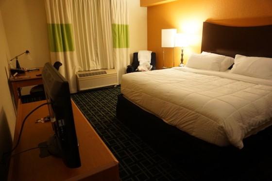Cama king na suíte familiar. Foto do quarto do Fairfield Inn by Marriot, com uma cama de casal king com roupa de cama branca e uma TV em frente
