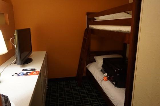 Área dos beliches no quarto. Foto das beliches no quarto do Fairfield Inn, com uma mala em cima da cama de baixo e uma TV ao lado.