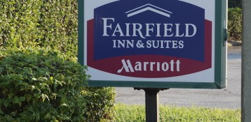 Foto da placa na entrada do hotel Fairfield Inn & Suites by Marriott, com as cores do Marriott (azul e vinho)