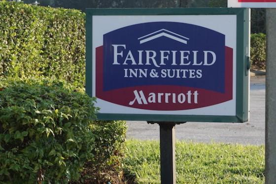 Plaquinha discreta na entrada do hotel. Foto da placa na entrada do hotel, com as cores do Marriott (azul e vinho)