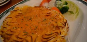 Foto da Shepperd's Pie do Finnegan's no prato, coberta com queijo gratinado