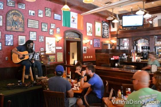 Foto de um cantor se apresentando ao vivo no interior do pub
